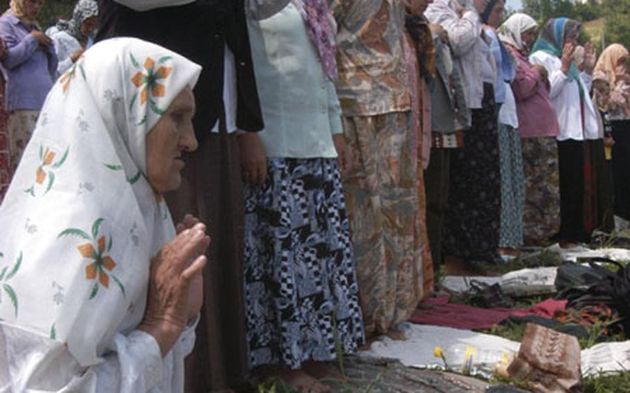 Sida Mehanovic, too weak to stand, prays over a picture of her missing family members at the eighth Srebrenica memorial ceremony at the nearby town of Potocari on Friday. Most of the 7,500 to 10,000 men killed after the fall of Srebrenica on July 11, 1995, were Muslim. A memorial is being built at the sight.