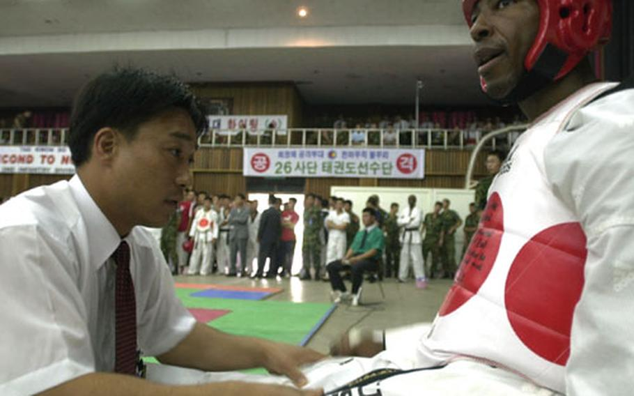 Spc. Louis Davis rests in between a second-round match at the ROK-U.S. Friendship Tae Kwon Do competition.