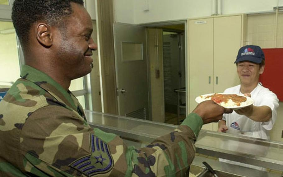 Staff Sgt. Rodney Reed, 35th Fighter Wing, is served lunch at Misawa's Grissom Dining Hall by Toru Okita, a food service specialist. The dining hall is one of more than 30 activities that earned the 35th Services Squadron the LeMay award.