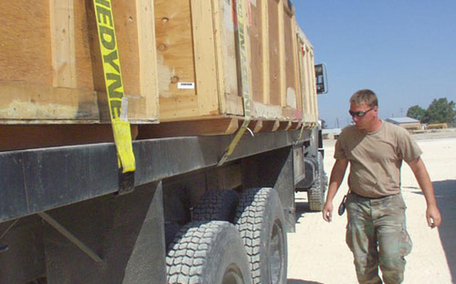 A Navy Seabee on Monday walks past a truck loaded with crates filled with tents used for a fleet hospital at Naval Station Rota in Spain.