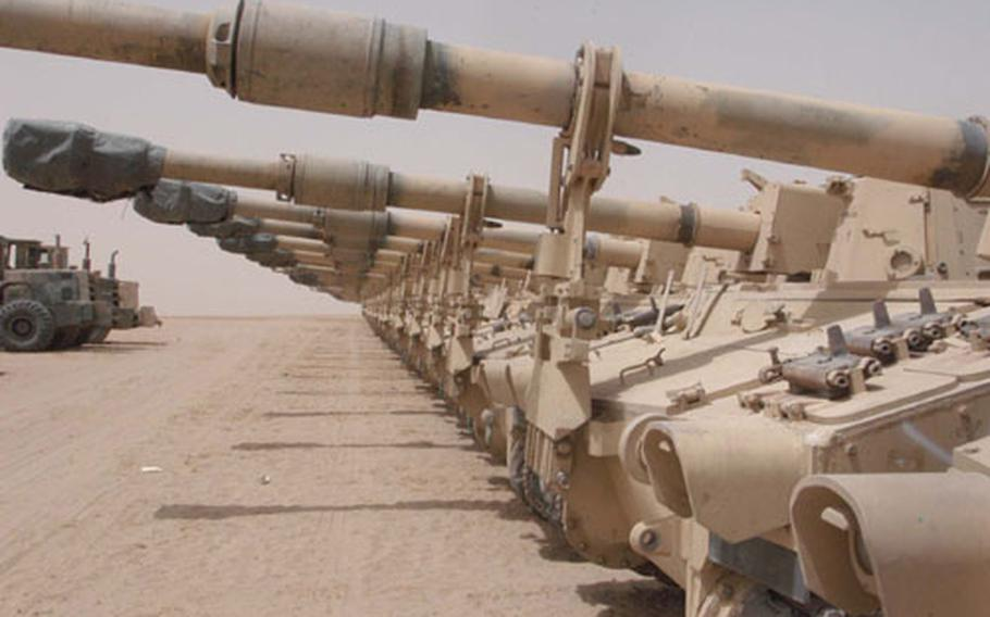 Tracked vehicles line up in the flat desert at Camp Arifjan, Kuwait, until they're loaded on ships and sent home. Soldiers are bringing back thousands of vehicles big and small from Iraq for a washdown and repairs before they're loaded up and shipped out.