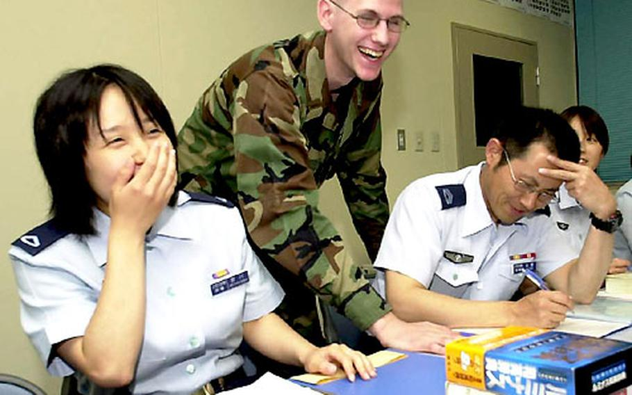 Staff Sgt. Izumi Miyakawa, left, of the Japanese Air Self-Defense Force shares a laugh with 2nd Lt. Chris Kuchma, standing, and Tech Sgt. Hideyuki Sato during as English language class at a JASDF classroom.