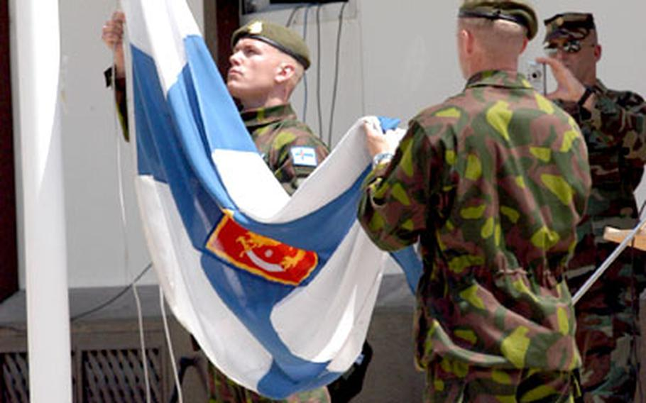 Finnish troops lower their flag at Monday's departure ceremony at Eagle Base.