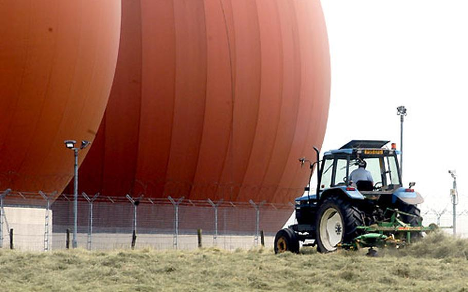 A farmer tends a field beneath the towers at RAF Croughton, England. The communications base has plans to improve and preserve the base ecology.