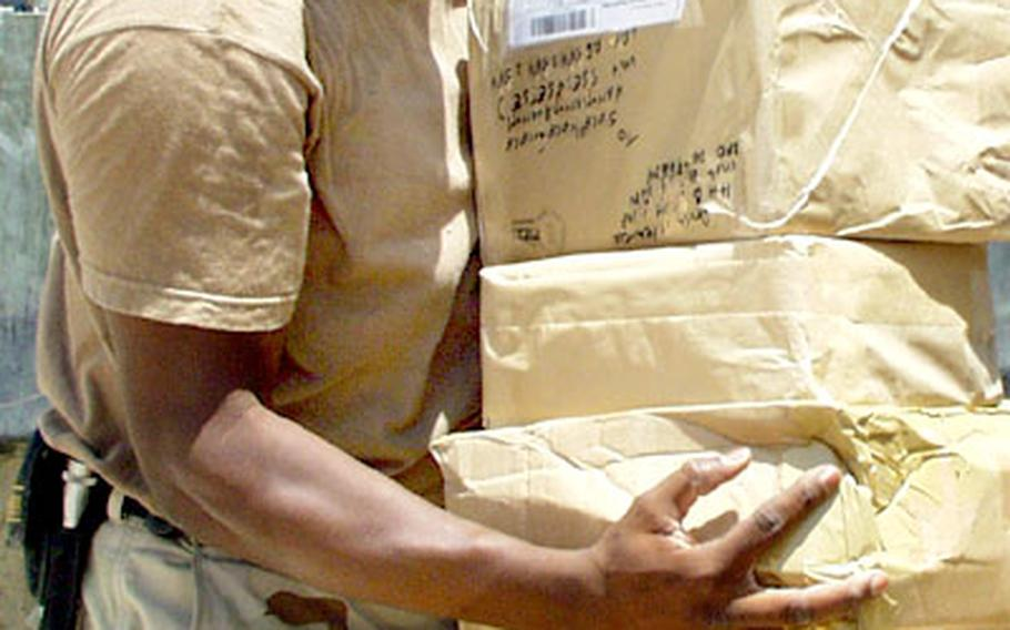 Sgt. Jerome Patterson, an Army reservist with the 912th Postal Company, unloads several packages from a truck that arrived minutes earlier at the front door of the facility at Baghdad International Airport that processes the mail for the 1st Armored Division.