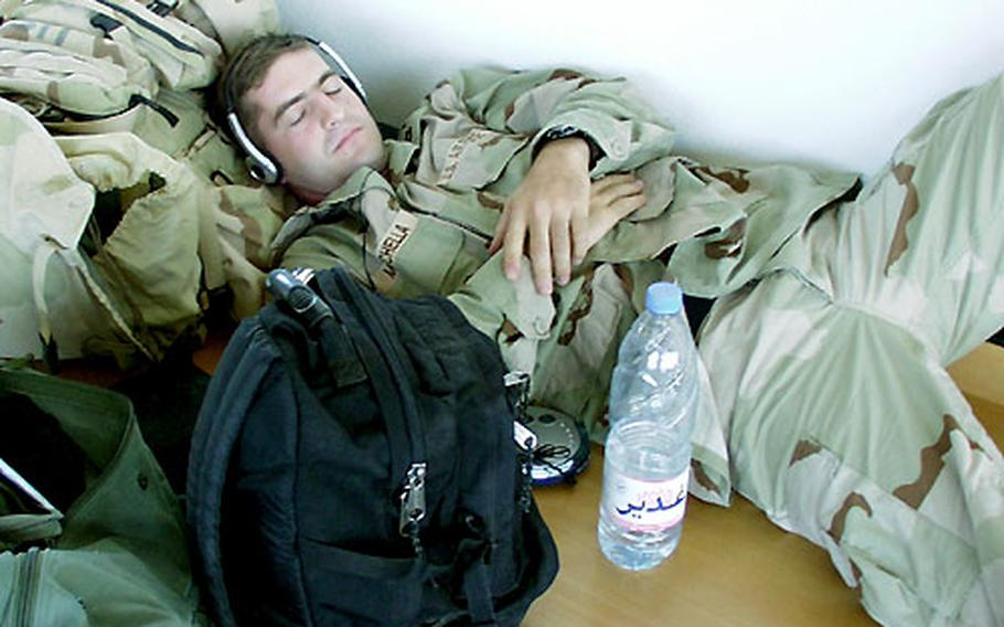 """Air Force Capt. Robert Moschella, with the 13th Air Support Operations Squadron at Al Asad airfield in Iraq, tries to catch some sleep while waiting Monday for a flight out of Ramstein Air Base, Germany, back to """"the box."""""""