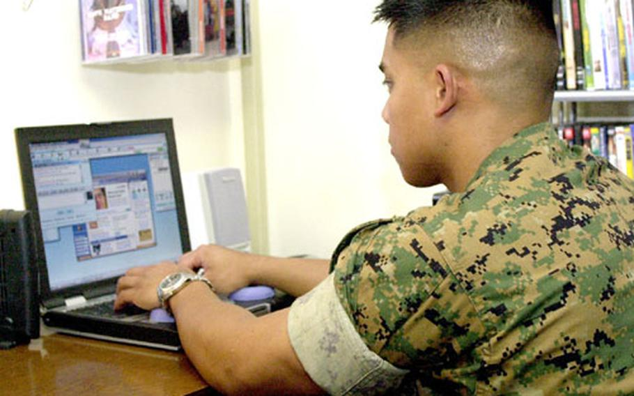Staff Sgt. Edward Tiglao uses his new cable modem Internet connection to chat online with his family. The broadband connection has brought an exciting change in the quality of life for Marines at Camp Fuji.