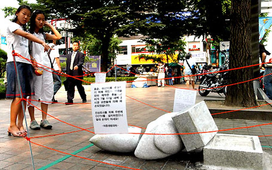 Two South Korean girls stand Tuesday afternoon looking at a toppled, vandalized monument on Chongno Street in Seoul.