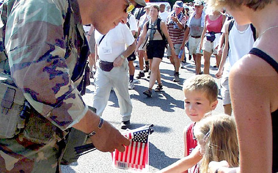Staff Sgt. Paul Meacham of 1st Battalion, 4th Infantry Regiment at Hohenfels, Germany, hands out American flags to kids after completing a 25-mile road march Wednesday.