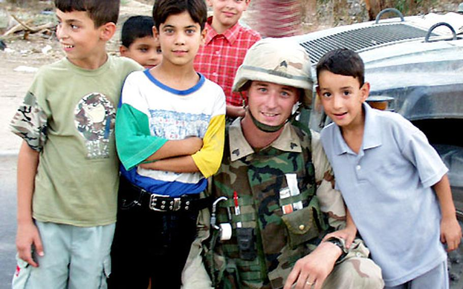 Almost everywhere American patrols go in Baghdad, they're greeted by smiling and waving Iraqi children. When they see a camera, they demand to get a picture taken. Sgt. George McGraw, a medic with the 2nd Battalion, 37th Armor Regiment that's part of the 1st Armored Division's 1st Brigade, was happy to pose with them.
