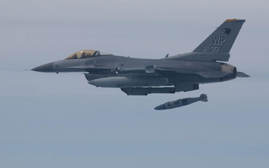 """In a training flight over South Korea earlier this month, a U.S. Air Force Block 30 F-16C fighter drops two precision-guided """"smart bombs"""" on a target range on Chik-Do Island. The Block 30's of the 80th Fighter Squadron out of Kunsan Air Base were recently fitted with the gear necessary to make use of the smart bombs, called JDAM, or Joint Direct Attack Munition."""