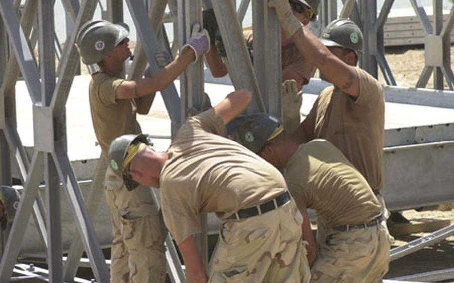 Seabees from Naval Mobile Construction Battalions 133 and 7 construct a bridge bay in Zubaydiyah, Iraq. The Seabees are in the area to build a Mabey-Johnson bridge to replace one that was destroyed during Operation Enduring Freedom.
