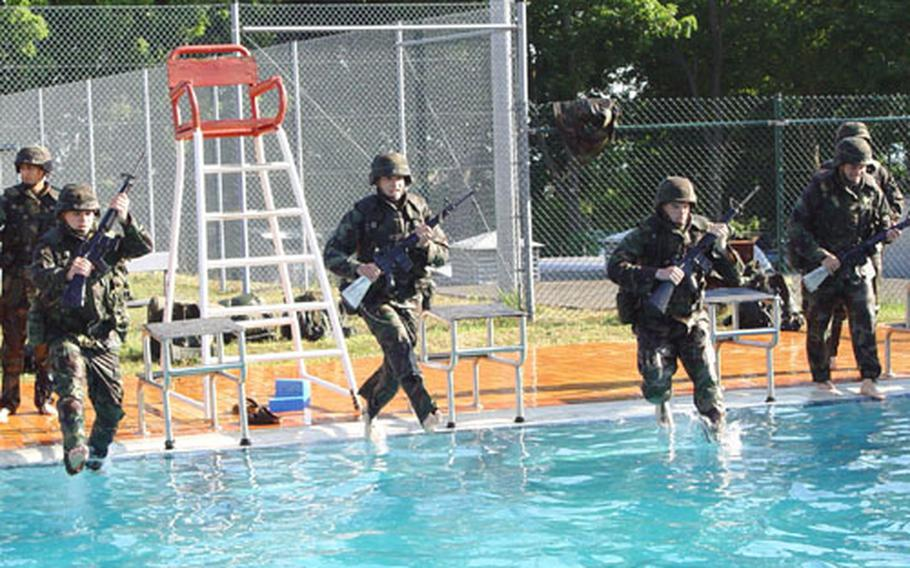 From left, 2nd Lt. Alvaro Gracia, Pvt. Dennis Dobbins, Sgt. Jonathan Willis and Sgt. Francisco Del-Valle, all of Company D, 701st Main Support Battalion, 1st Infantry Division, jump into a swimming pool during water survival training July 17th.