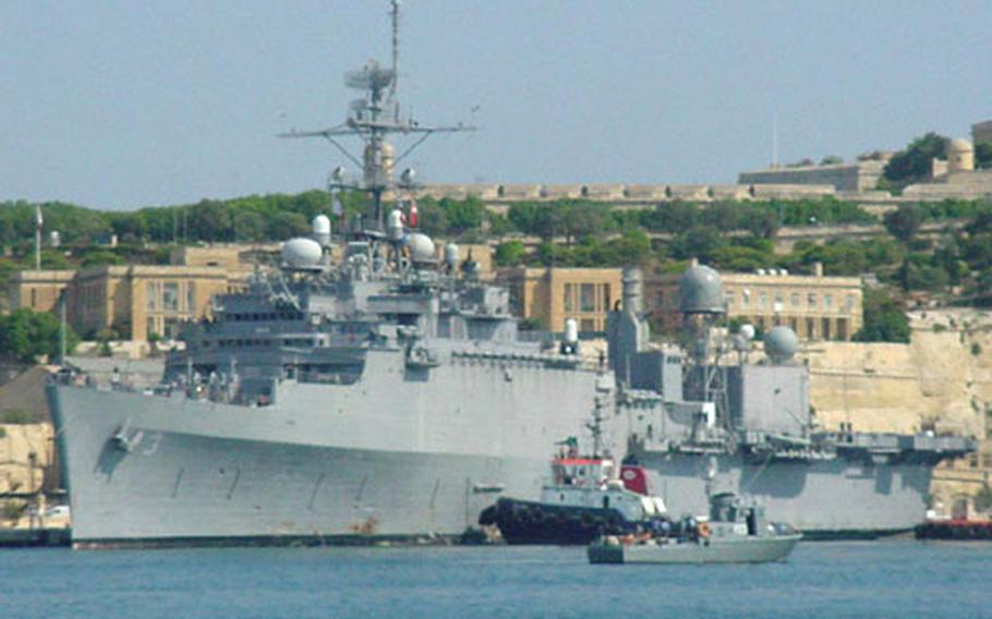 A tugboat helps ease the USS La Salle into the docking area in LaValetta, Malta, last week, where it is scheduled for repairs.