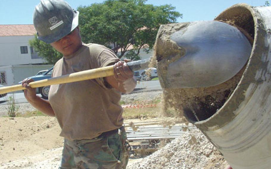 Petty Officer 3rd Class Diana Standing, a Navy Seabee with Naval Mobile Construction Battalion 26, fills a cement mixer on Thursday outside the Bachelor Officer's Quarters at Naval Station Rota, Spain.