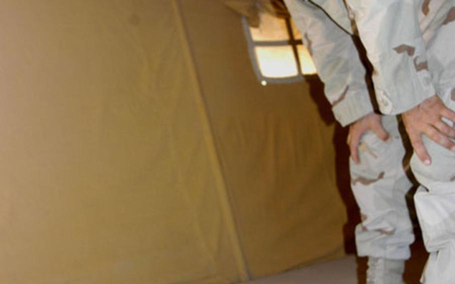 Sgt. Michael Trapp, acting as fire marshal for Camp Virginia, Kuwait, examines damaged electrical wiring in a recently vacated tent. Troops passing through have tampered with the electrical lines, causing a fire hazard.
