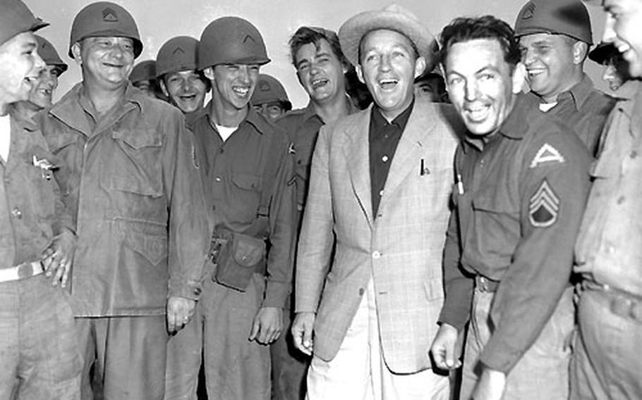 Bing Crosby poses with members of the 7th Army Flight Det.
