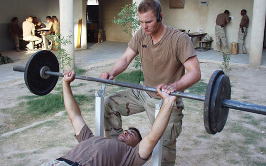 Pfc. Joe Raser spots for Pfc. Jason Al-Jehani during bench presses at the compound Company A, 1st Battalion, 508th Infantry Regiment, calls home in the town of Hawija in northern Iraq.