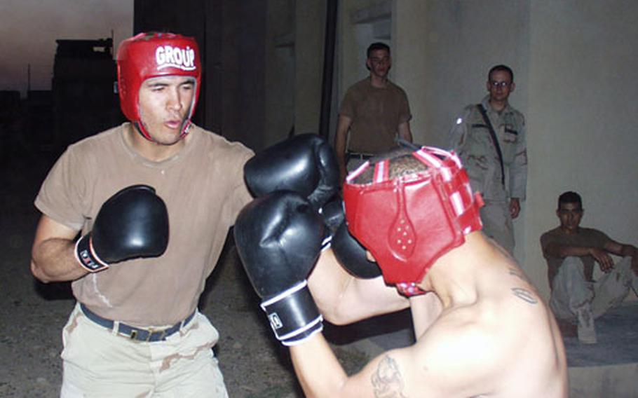 Pfc. Reinaldo Alvarez, left, tries to land a punch against Staff Sgt. Rafael Ortiz during a boxing match at the compound in Company A, 1st Battalion, 508th Infantry Regiment's compound in Hawija, Iraq.