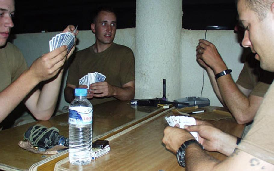 Soldiers who like playing cards don't let issues such as electrical power outages get in the way. Pfc. Matt Freeburn, left, and Pfc. Phil Knight teamed up against Lt. Joel Ellison and Sgt. Shane Wilson in a game of spades. When the electricity went out, the players brought out flashlights.