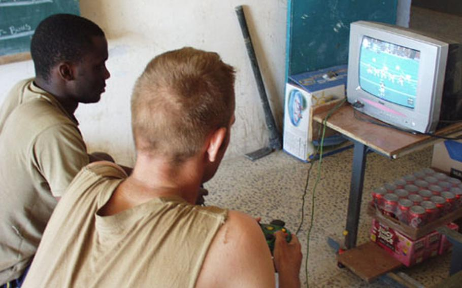 Sgt. Racean McMillan and Pfc. A.J. Ashley play a game of football via Xbox at the camp in Jar Silah, Iraq, that Company C, 1st Battalion, 508th Infantry Regiment calls home.