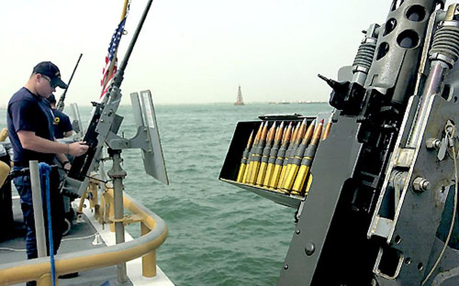 Petty Officer 3rd Class Jason Schmitz, 22, of Jacksonville, NC., prepares a .50 caliber machine gun onboard the Coast Guard cutter Baranof in the Persian Gulf.