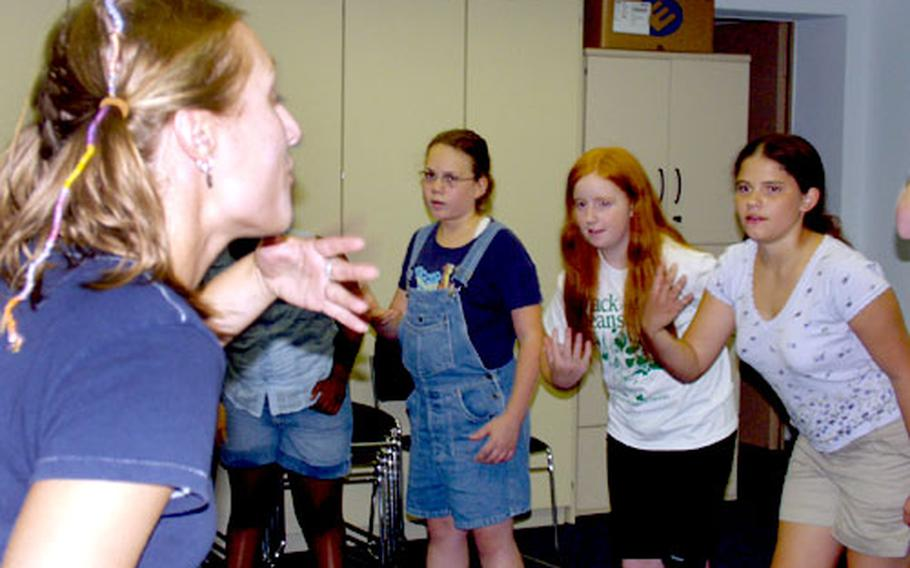"""Leigh Lingnofski, 22, from Appleton, Wis., gives children from Darmstadt a crash course in playing beggars in the Missoula Children's Theatre production of """"Cinderella."""""""