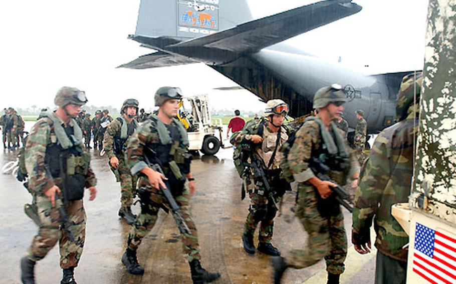 Marines with the FAST team out of U.S. Naval Air Station Rota, Spain, offload from a Kentucky Air National Gaurd C-130 in Lungi, Sierra Leone, on their way to Liberia.