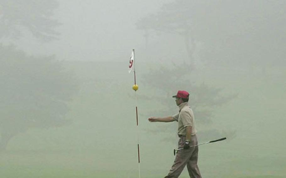 Thick fog serves as a placid backdrop for this golfer on the 9th hole at Gosser Memorial golf course at Misawa Air Base, Japan.