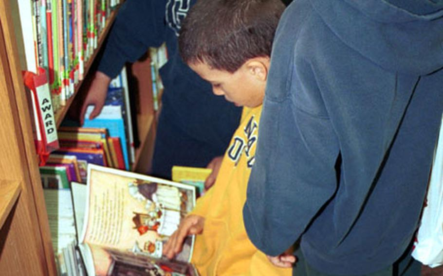 Three children participating in the summer reading program at Naval Air Station Keflavik, Iceland, select books from the base library.