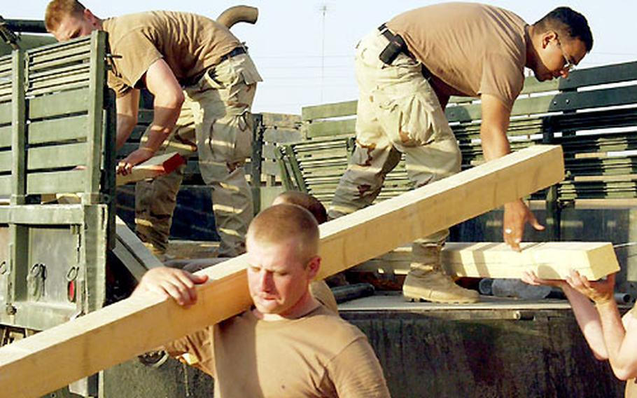 Soldiers assigned to Company A, 1st Battalion, 508th Infantry Regiment keep busy with tasks such as getting material to make their camps more secure. Some of this lumber was going to be used to build an outhouse.