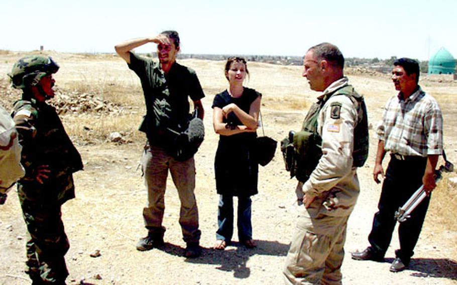 Lt. Col. Dominic Caraccilo talks with Australian journalists and their Iraqi translator near Kirkuk, Iraq. Caraccilo, commander of 2nd Battalion, 503rd Infantry Regiment, and his soldiers had stormed the area after getting reports of someone carrying a rocket-propelled grenade.