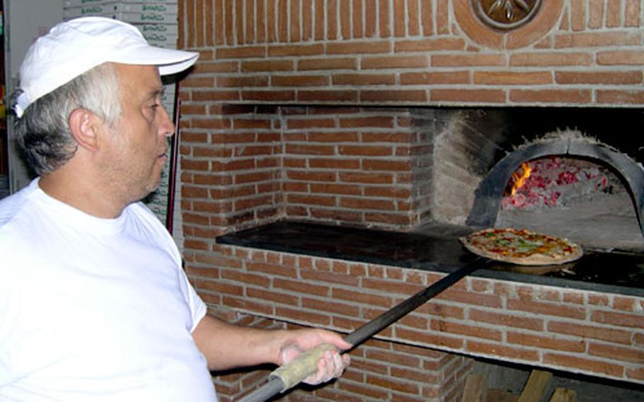 Giuseppe Grane of the Punto di Incontro restaurant in Gricignano di Aversa, Italy, pulls a pizza Margherita from his traditional wood-fired brick oven.