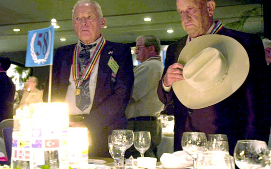 """Korean War veterans Ronald W. Schaller, of Plainfield, Ill., and Mark Watson, of Manning, La., during a moment of prayer for soldiers who died during the Korean War. About 800 veterans from 22 nations gathered at the Hyatt Hotel Friday night for the USO's """"Salute to Heroes."""""""