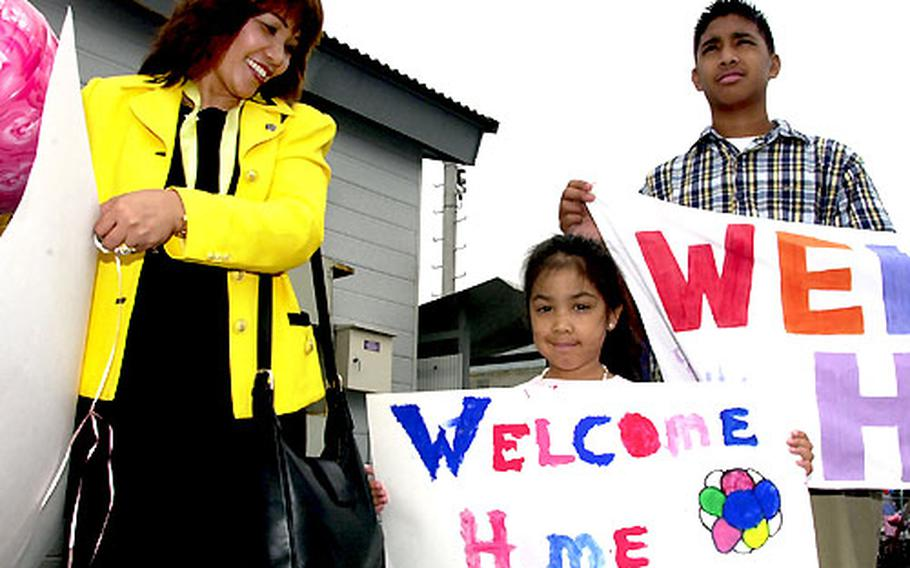 Melanie Dua, daughter Anna Victoria and son Vijay hold up signs to welcome back their sailor from the USS Gary.