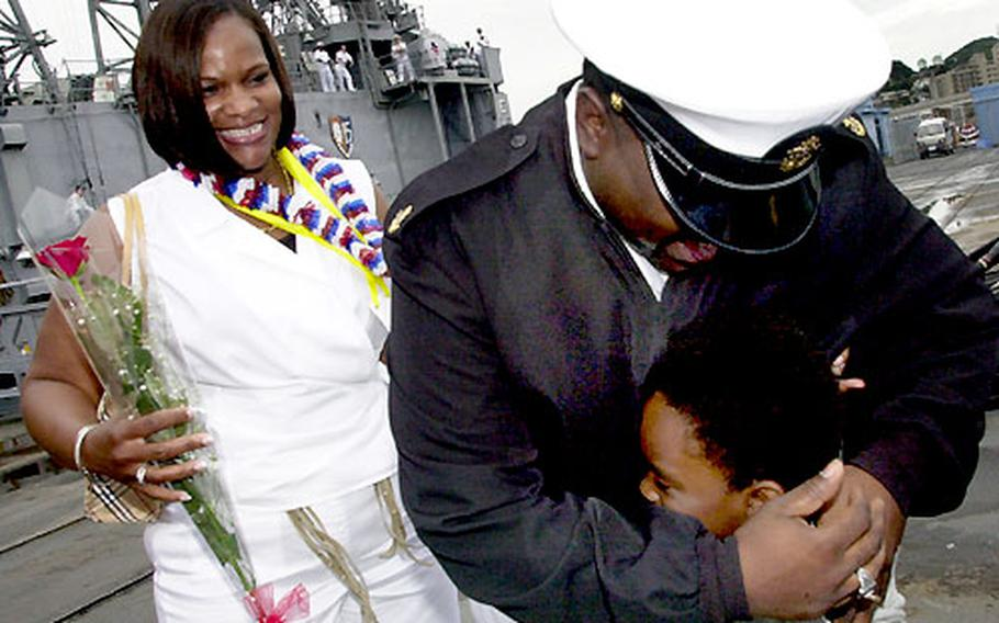 Felicia Cambridge smiles as she watches her husband, Chief Petty Officer Ricky Cambridge from the USS Gary, give daughter Brittney a big hug upon his return from the Persian Gulf.