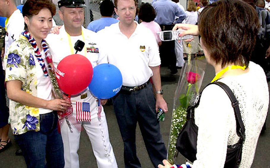 Yoshiko Mannion takes a picture of her husband, Senior Chief Petty Officer Sean Mannion, and friends at his homecoming to Yokosuka Naval Base Saturday.