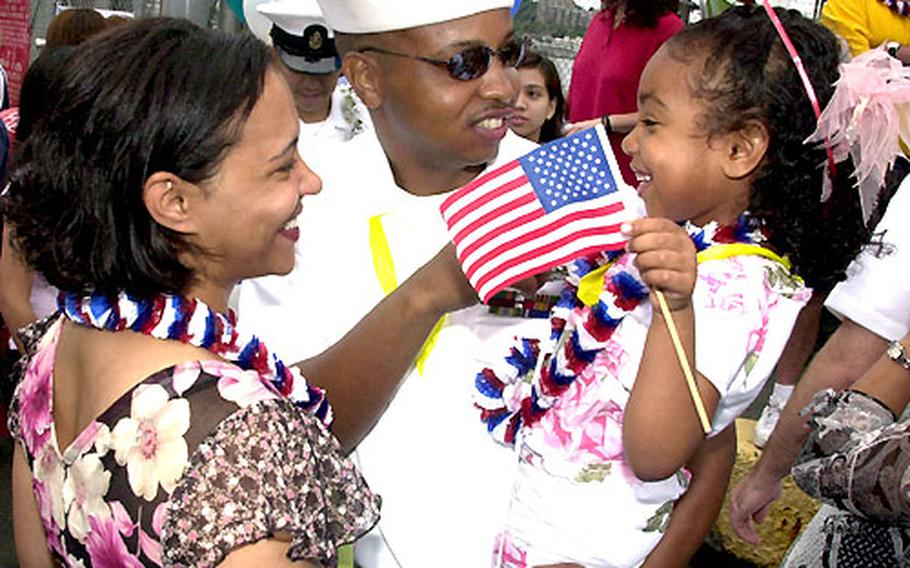 Sinalman 1st Class David Sudler is reunited with daughter Kianna and wife Kharisma at Yokosuka Naval Base Saturday.