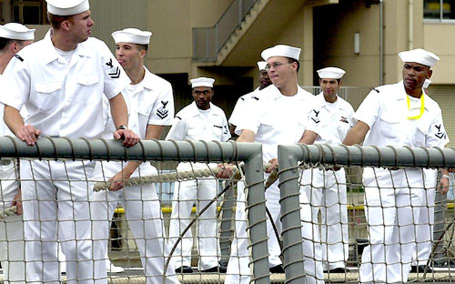 Sailors of the USS Gary pull in the slack from the aft mooring line at Yokosuka Naval Base upon returning from the Persian Gulf.