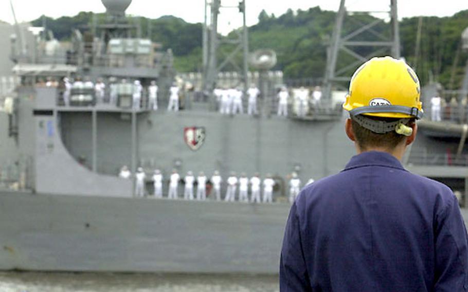 A Japanese shipyard worker waits for the USS Vandergrift to moor pierside at Yokosuka Naval Base.