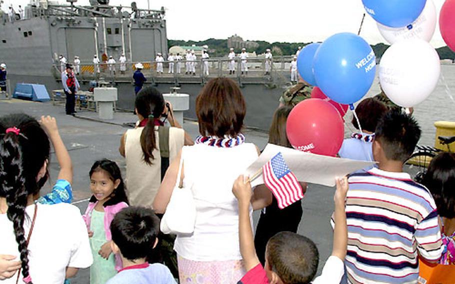 Families of sailors of the USS Vandergrift wait for the ship to moor Saturday at Yokosuka Naval Base.