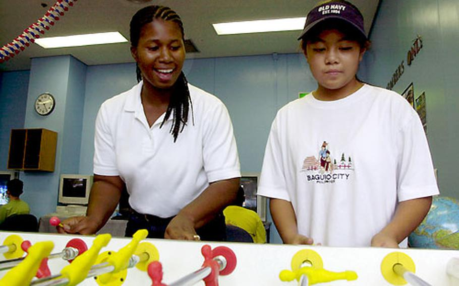 Jennifer Reed, the Teen and Pre-teen centers' supervisor at Sasebo Naval Base's Hario Housing Village, teams with Vanny Angeles, 11, during foosball action Wednesday afternoon at The Den.