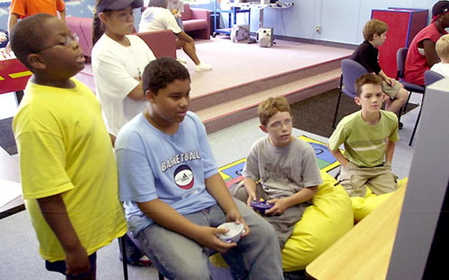 Playstation video games are a huge hit on the big-screen television at The Den. Wednesday afternoon, Jordan Green, 12, sitting at left, plays against Malcolm Hylton, 11, sitting at right, as Leonard Outz, 10, standing at left, Vanny Angeles, 11, standing in center, and Sam Person, 11, far right, look on.