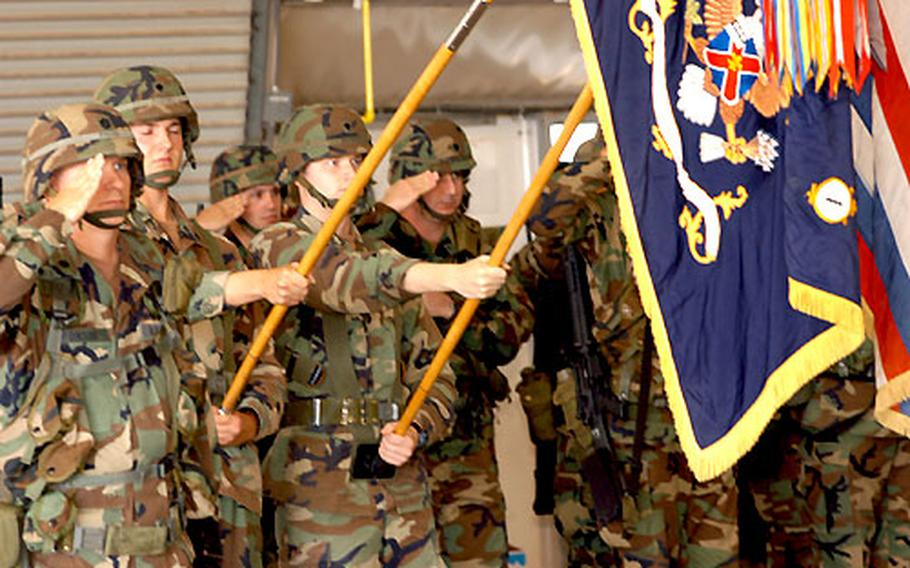 Troops salute during the Transfer of Authority ceremony Monday at Camp Bondsteel, Kosovo.