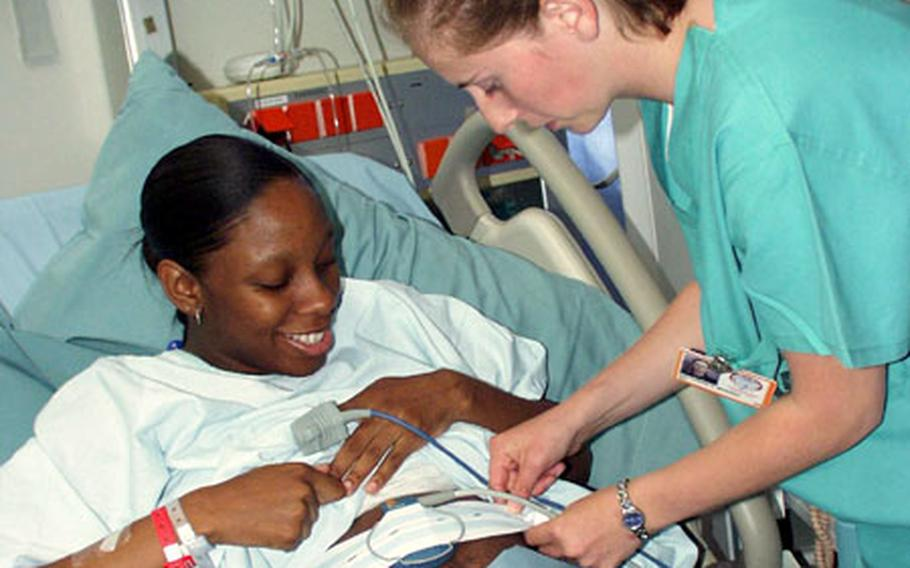 Carrie Bowden, an ROTC cadet, checks on LaBreshia Hudson's baby heart monitor in the labor-and-delivery ward at Landstuhl Regional Medical Center in Germany.