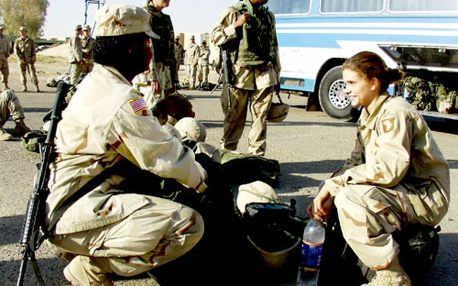 At Qayyarah West Airfield in Iraq, Spc. Jessica Middleton, from Charleston, N.C., left, and Pfc. Cristal Schorn, from Schaumberg, Ill., both with the 1st Brigade of the 101st Airborne Division, prepare Monday to board the bus for northern Iraq.