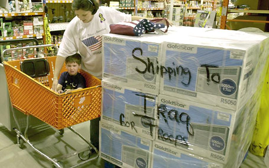 Frankie Mayo and her two-year-old son Devin at a Delaware Home Depot store, where she bought a pallet full of air conditioners to send to troops in Iraq.