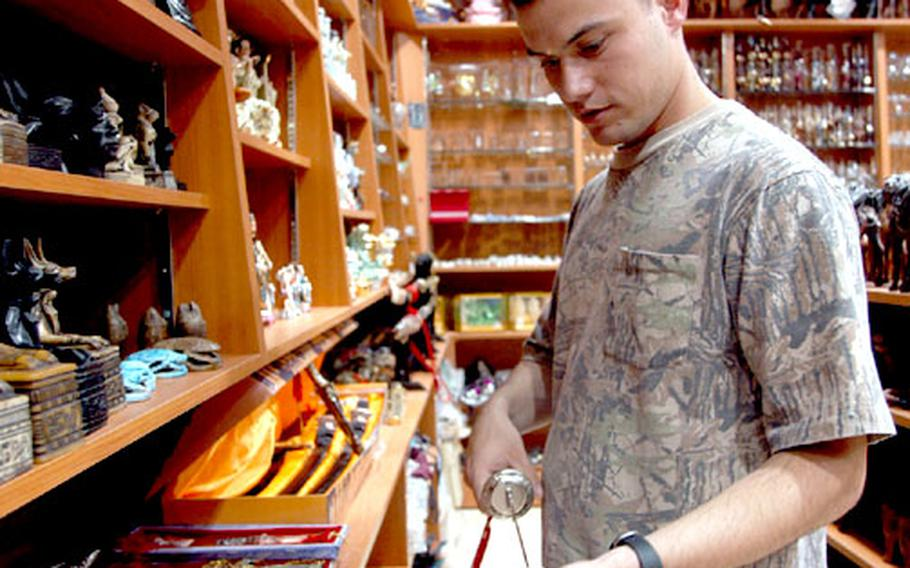 Sgt. Steve Speissegger, a paralegal with 3rd Personnel Command from Summerville, S.C., looks at daggers and swords at a shop in Fahaheel, Kuwait during an MWR shopping trip for servicemembers.