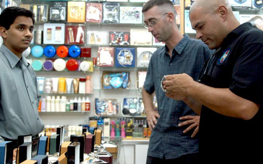 Servicemembers look over possibly real Rolex watches at a shop in Fahaheel