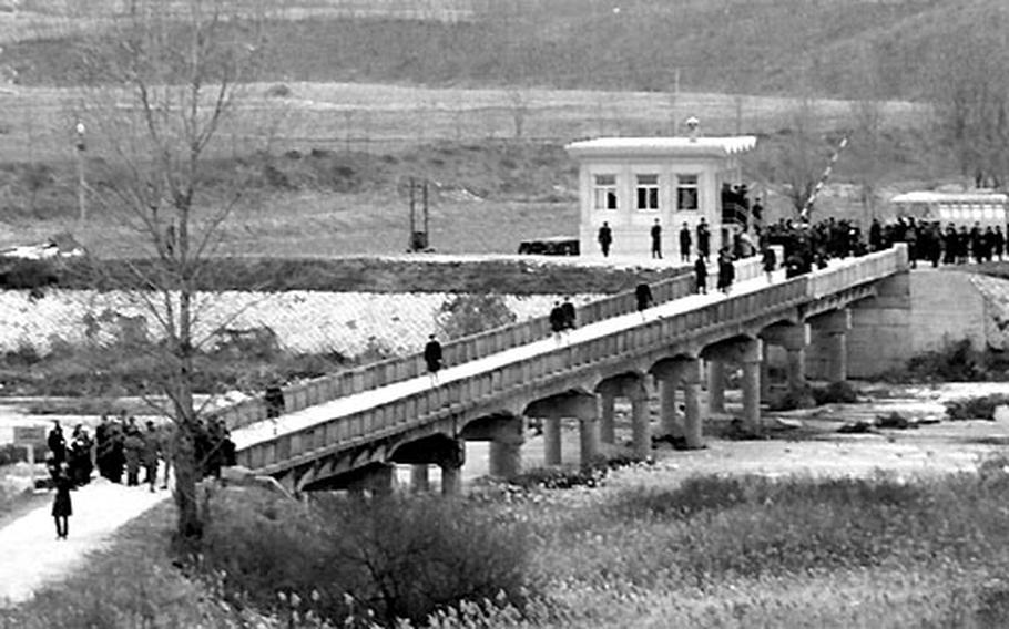 USS Pueblo crew members cross the bridge from North Korea at Panmunjom after their release on December 23, 1968.